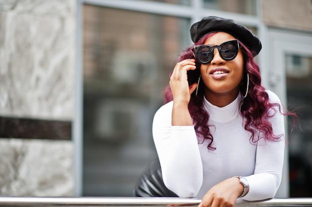 Большая мама плюс размер афроамериканской модели в черных солнцезащитных очках, берете и кожаной юбке позирует на открытом воздухе и разговаривает по телефону.