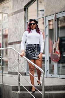 Большая мама плюс размер афроамериканской модели в черных солнцезащитных очках, берете и кожаной юбке позировала на открытом воздухе.