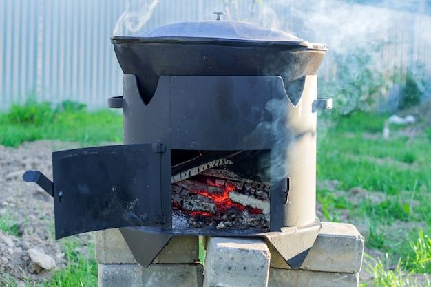 Big metal cauldron pot on movable stove outdoors