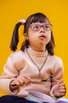 Большая металлическая ложка. заинтересованная девушка с хромосомной аномалией в розовом свитере и ест из глубокой миски
