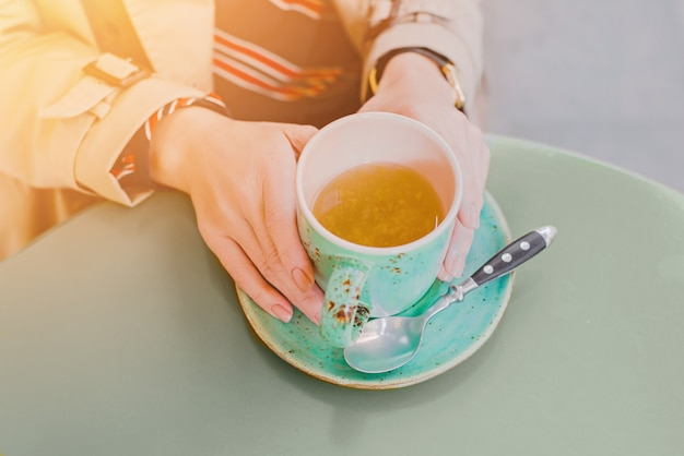 Big mint green tea cup in woman's hands in cafe