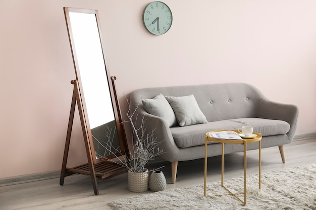 部屋の色の壁の近くにソファのある大きな鏡