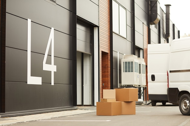 Big modern warehouse for parcels and loads with delivery van near the gate