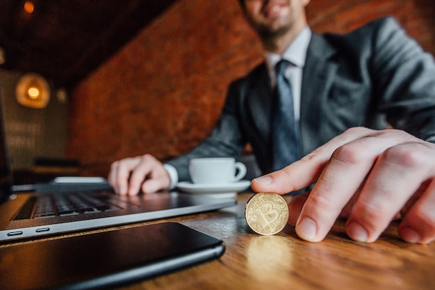 Big money businessman in suit holds a bitcoin and sits at the table with laptop