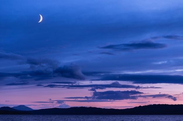 夕方の湖の上の青い空の大きな月