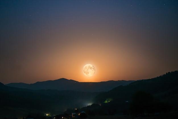 Большая луна поднимается на ночном небе со многими звездами над горным хребтом