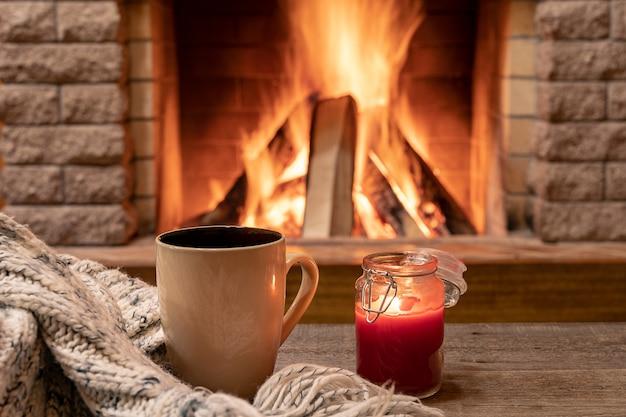 Big mug with hot tea and a candle