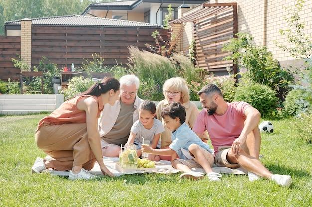 暖かい夏の日に裏庭の芝生でピクニックをしている大規模な多世代家族