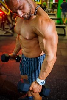 Большой мускулистый мужчина с голым торсом с гантелями в руках. мужчина в тренажерном зале качает бицепс