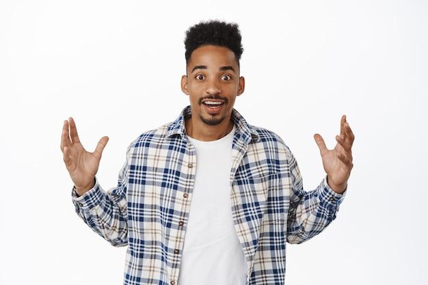 ビッグニュース。握手している驚いたアフリカ系アメリカ人の男は、手に大きくて背の高いものを見せ、驚いて微笑んで、白い上に立っている巨大な何かを説明します。コピースペース