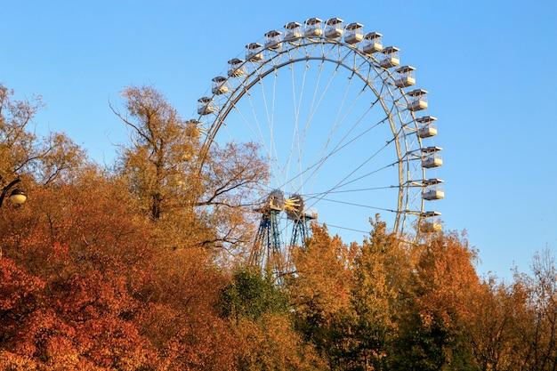 Большое колесо обозрения в осеннем парке на голубом небе