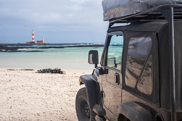 Big off road vehicle from black high strong car explore the beach and look at the lighthouse. alternative way of travel and lifestyle for traveler in wanderlust