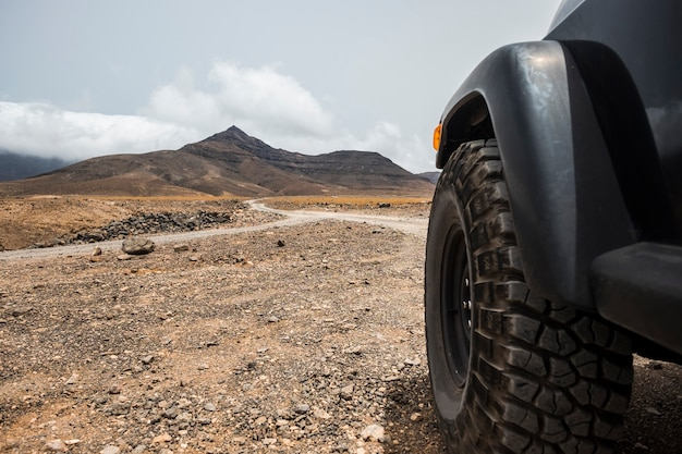 Big off road wheel from black high strong car explore the desert and the mountains in the country side. alternative way of travel and lifestyle for traveler in wanderlust