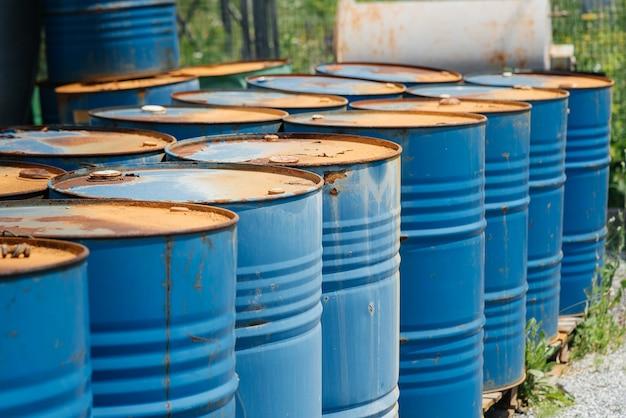 Бочки для масла большие, синие. химические бочки на открытом складе. ржавые бочки. бочка для масла.