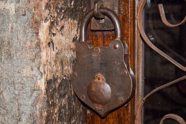 Big old padlock on wooden door