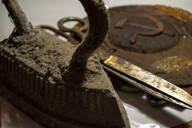 Большие старые потные ножницы и старинный утюг, нагретый на плите.