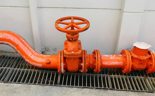 A big orange color water supply main pipeline with a stopcock valve against a concrete wall.