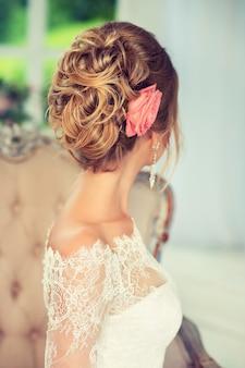 Пышная бледная роза и изящно собранные локоны на пышной свадебной прическе.