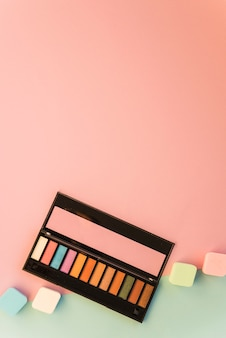 Big palette of make up with colorful sponge on dual backdrop