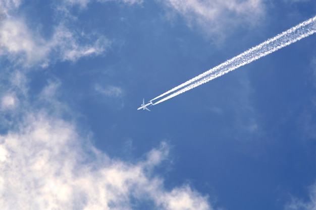 Big passenger supersonic plane with two jet engines flying high in blue sky with white clouds and leaving long white trace