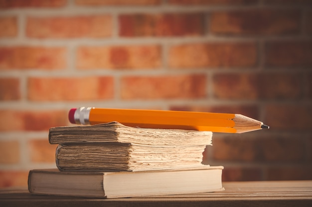 Big pencil and old books on wooden table
