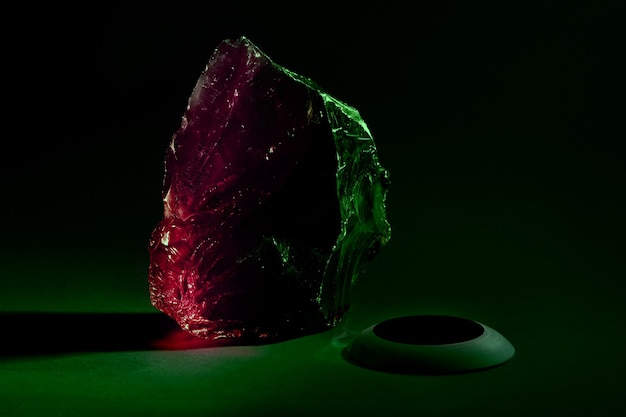 Big piece of glass with colored lights over dark background