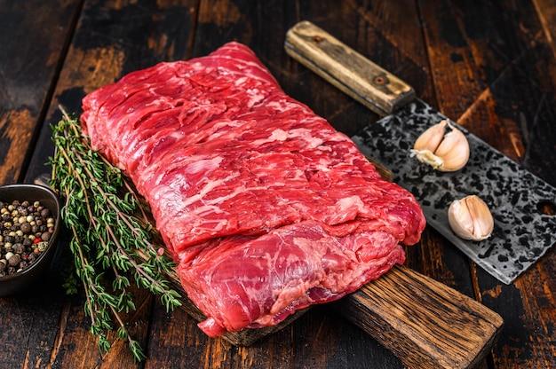 Большой кусок сырой говяжьей грудинки нарезать мясо с зеленью и мясным ножом