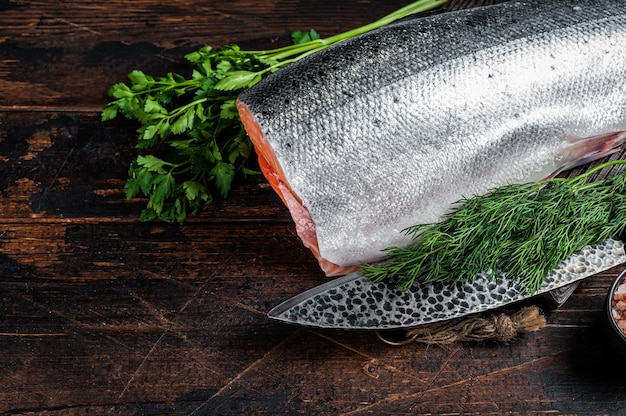 Большой кусок сырого лосося на деревянной разделочной доске с ножом шеф-повара. темный деревянный фон. вид сверху. скопируйте пространство.