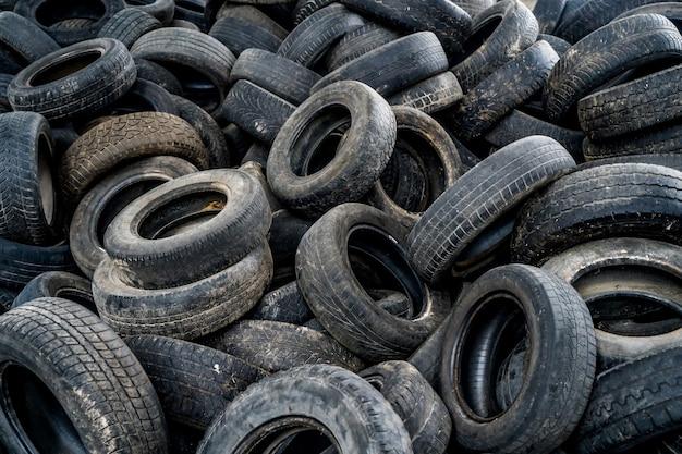 Большая куча автомобильных шин на сломанном заводе. множество черных резиновых покрышек на земле внутри старого огромного пустого здания.