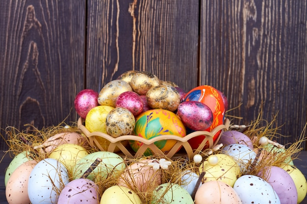 着色されたイースターエッグの大きな山。コピースペースと木製の背景に装飾的なイースターの休日の卵。