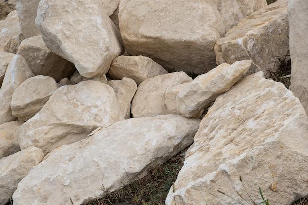 Большая куча больших камней песка кладя на том основании строительной площадки.