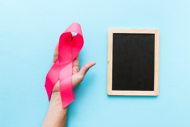 Big pink awareness ribbon in hand near the blank wooden slate on the blue background