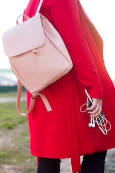 Big pink backpack and phone with headphones in the arm of the girl in a fashionable red coat