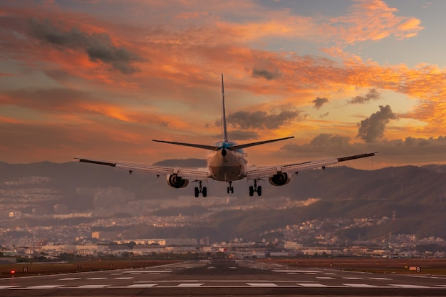 日没時に大阪伊丹国際空港に着陸する大型飛行機