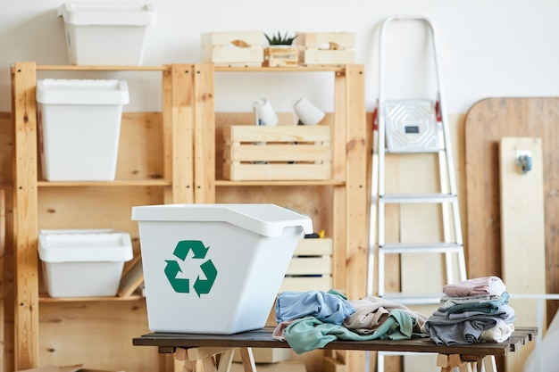 大きなプラスチックのゴミ箱と保管室のテーブルの上の古着