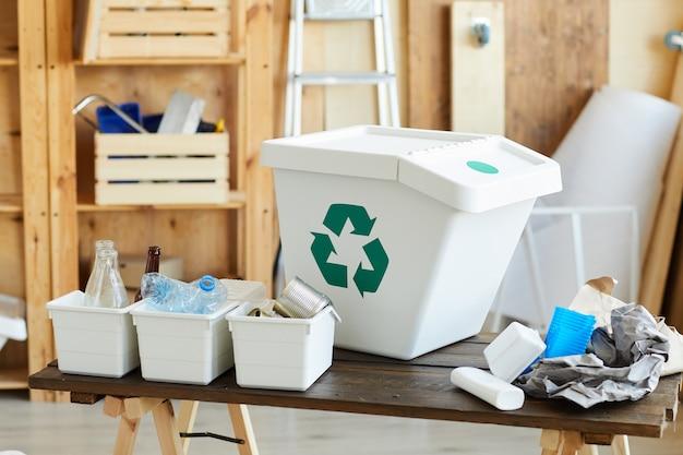 テーブルの上の小さな箱にゴミと分別された廃棄物のための大きなプラスチック容器