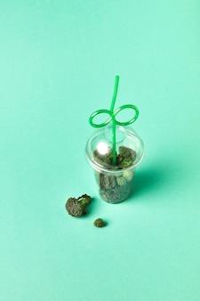 天然の生有機野菜が入った大きなプラスチックガラス-薄緑色の紙に緑色のブロッコリー