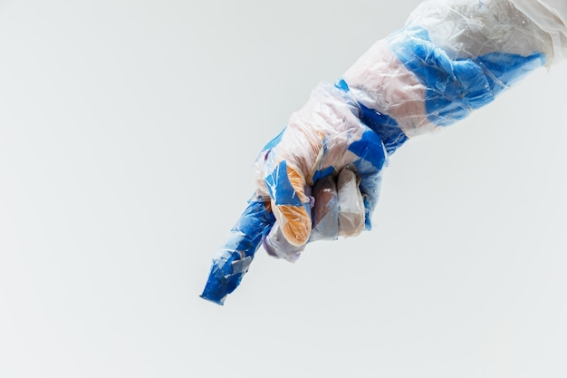 Big plastic hand made of garbage on white