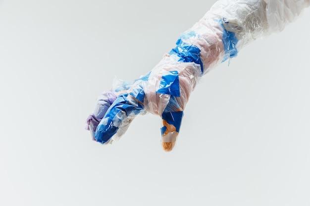 白い壁に隔離されたゴミで作られた大きなプラスチック製の手。ポリマーの過剰使用と過剰生産の結果。生態系の問題、汚染、リサイクル。人類にとって危険になりつつあります。