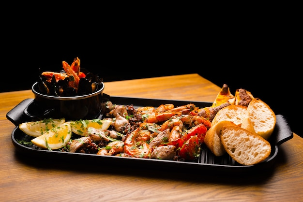Big plate with cooked and grilled tasty delicious sea food on wooden table