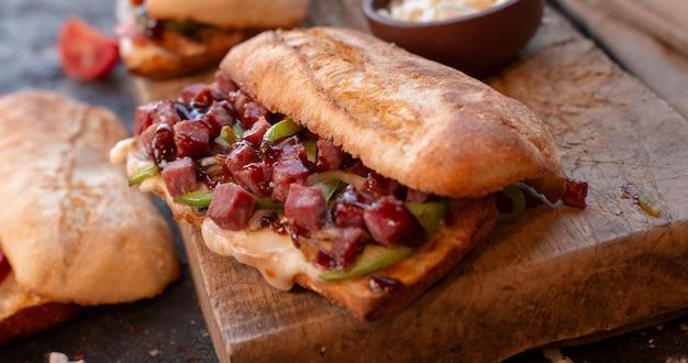 Большая порция сэндвича с багетом, полная смешанных колбас и овощей