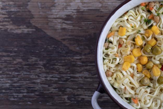 Una grande pentola di gustosi noodles con verdure su sfondo di marmo