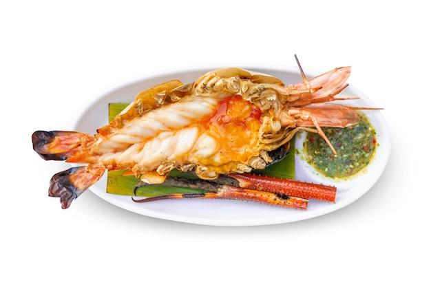 白い背景で隔離の白いプレートにスパイシーなシーフードソース、豪華なおいしいタイの伝統的な食べ物と大きなエビのバーベキュー