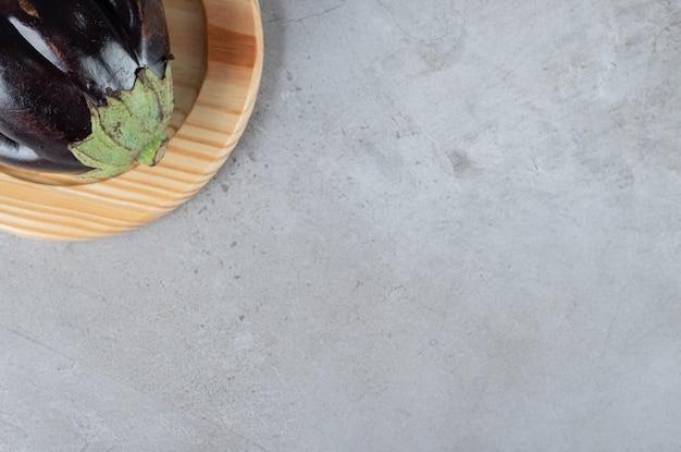 Una grande melanzana viola su una tavola di legno. foto di alta qualità