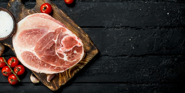 Big raw pork steak with tomatoes and spices on a black rustic table.