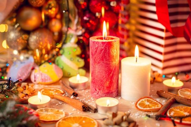 주위에 아름다운 크리스마스 장식과 함께 테이블에 큰 빨간색과 흰색 촛불