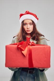 Большая красная коробка с бантом и подарками к праздникам рождество новый год красивая девушка. фото высокого качества