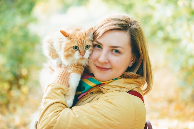 Big red cat in hands of girl in outdoor. beautiful portrait of woman with ginger cat in autumn colors. two lazy faces. fluffy pet in hands  big cat eyes close-up.