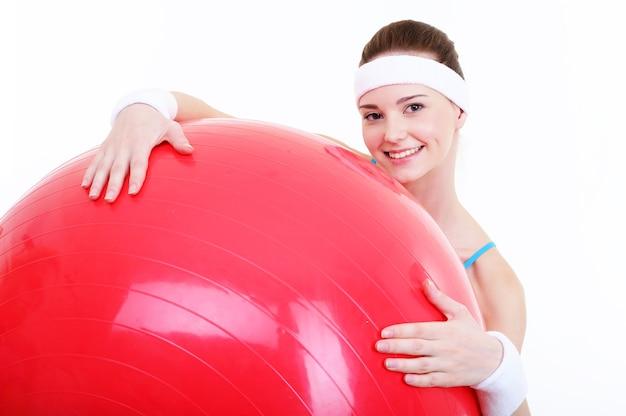 大きな赤いフィットボールと若い美しい幸せな女性の顔