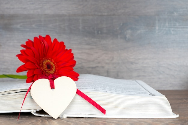 Big red flower with opened book and heart shape on rustic wooden table